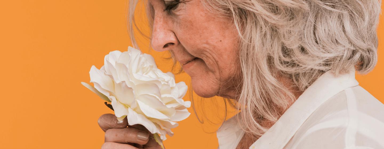 Uma senhora sentindo o perfume de uma flor